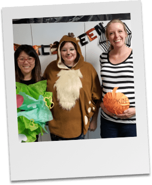 Grants team poses in Halloween costumes at staff party
