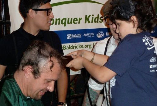 Dr. Dean Lee getting his head shaved to help fund childhood cancer research