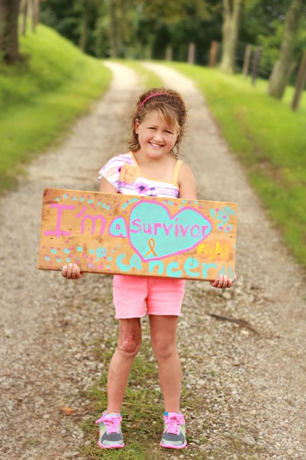 Chloe holding a cancer survivor sign
