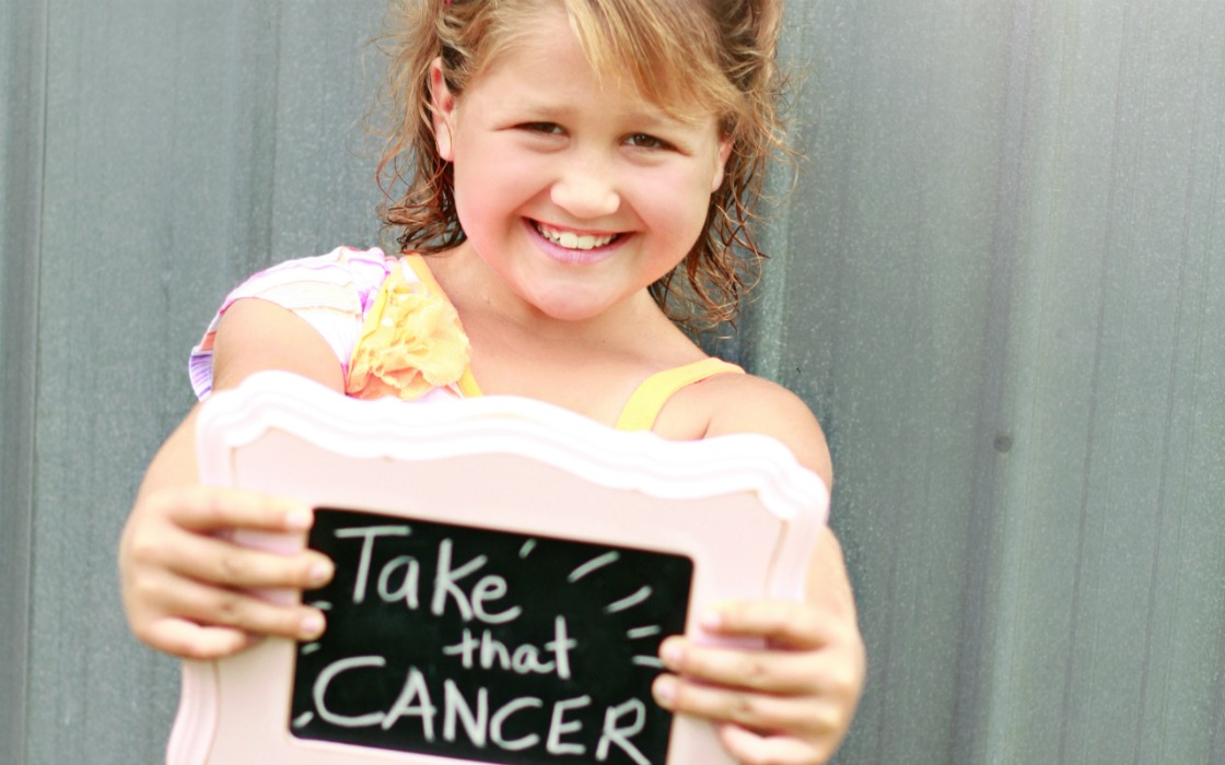 Chloe holding a sign that reads, 'Take that, cancer'