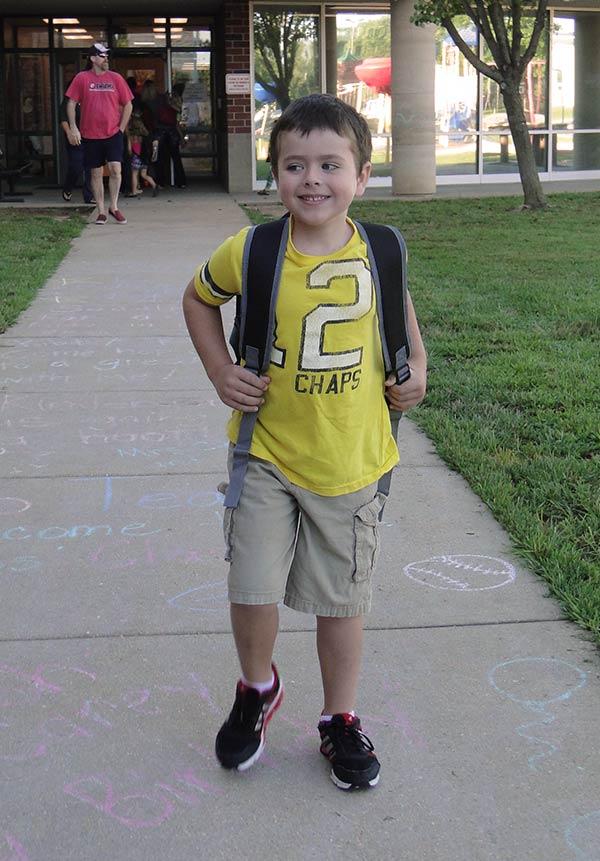 Hayden in front of his school