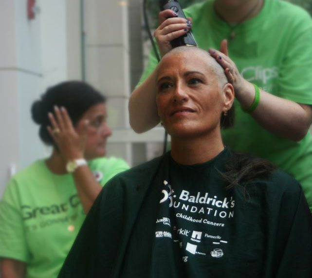 Leslie getting her head shave at the 46 Mommas Shave for the Brave