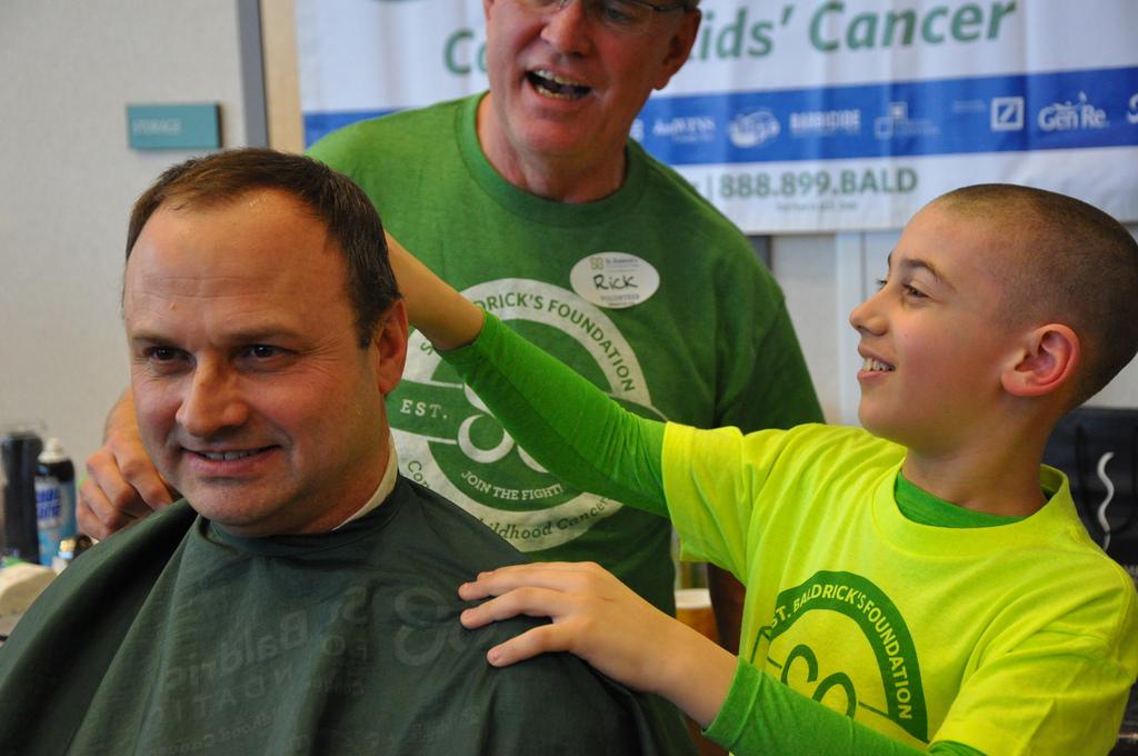 Son shaving his father's head