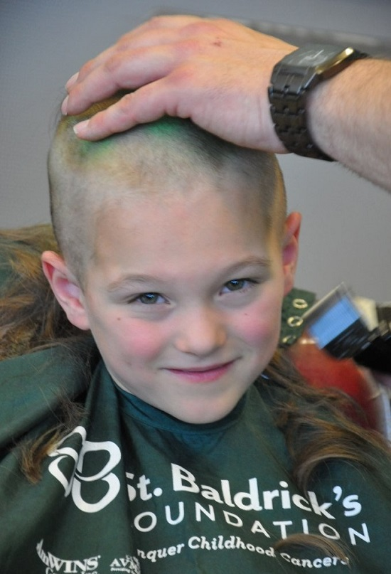 Young boy shaving head for cancer