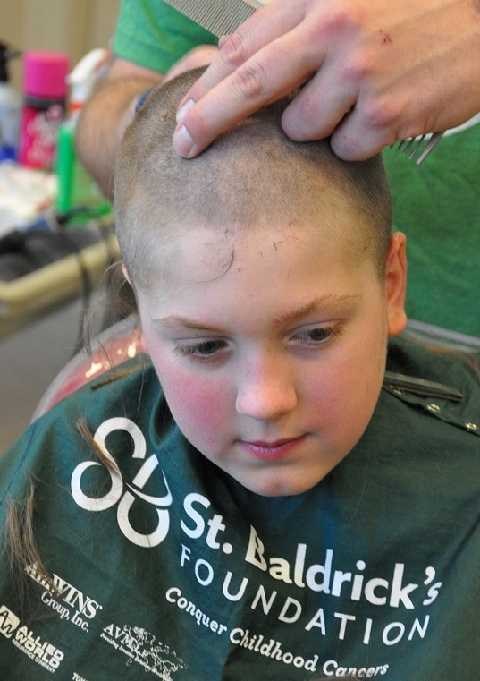 Boy looking pensive as his head is shaved