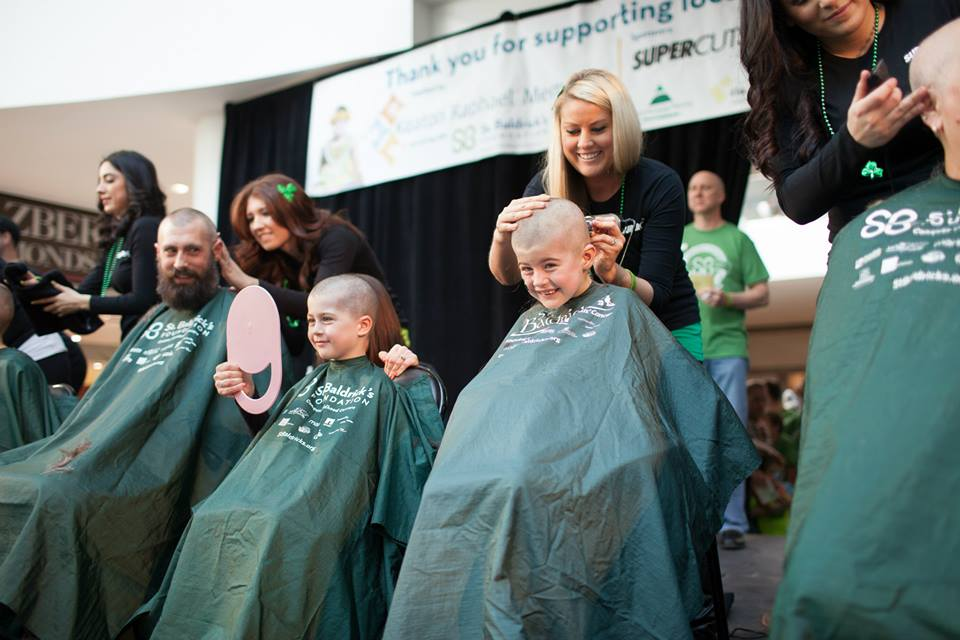 Kaela, Mara, and their dad getting their heads shaved
