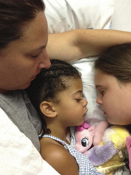 Carolyn and Rebecca sleeping in a hospital bed
