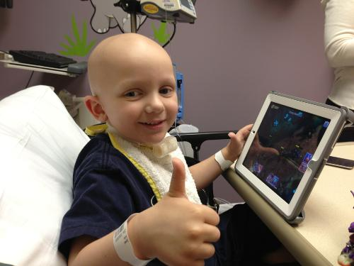Israel smiles and gives a thumbs up on his last day of chemo