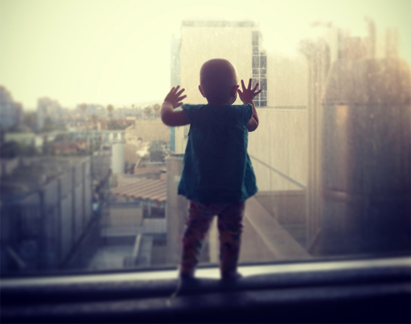 Lilly gazing out the hospital window while she was in treatment for childhood cancer