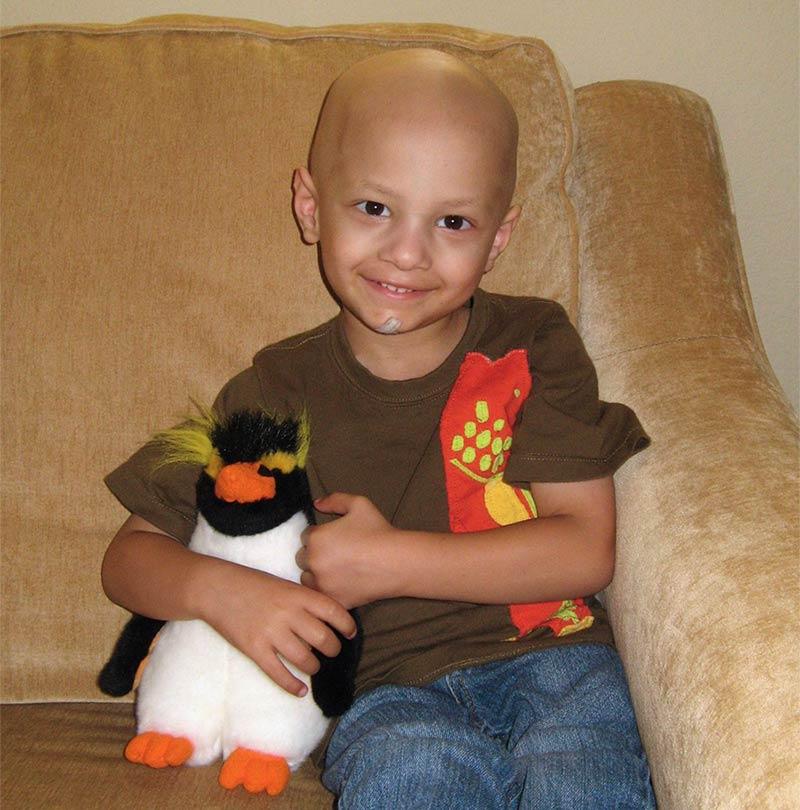 Micah holding a stuffed penguin
