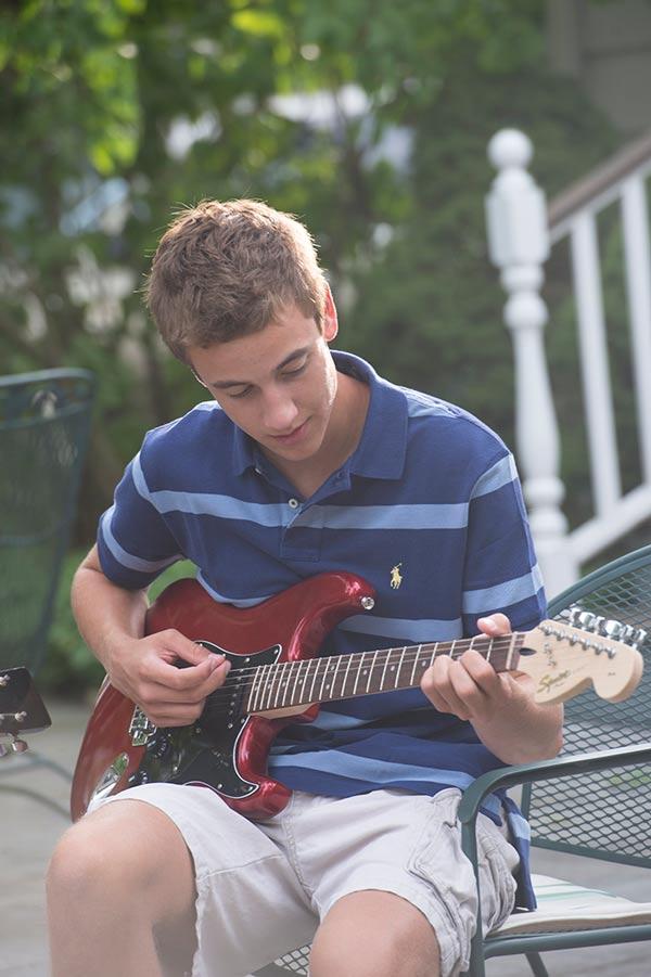 Ambassador Aaron plays guitar.
