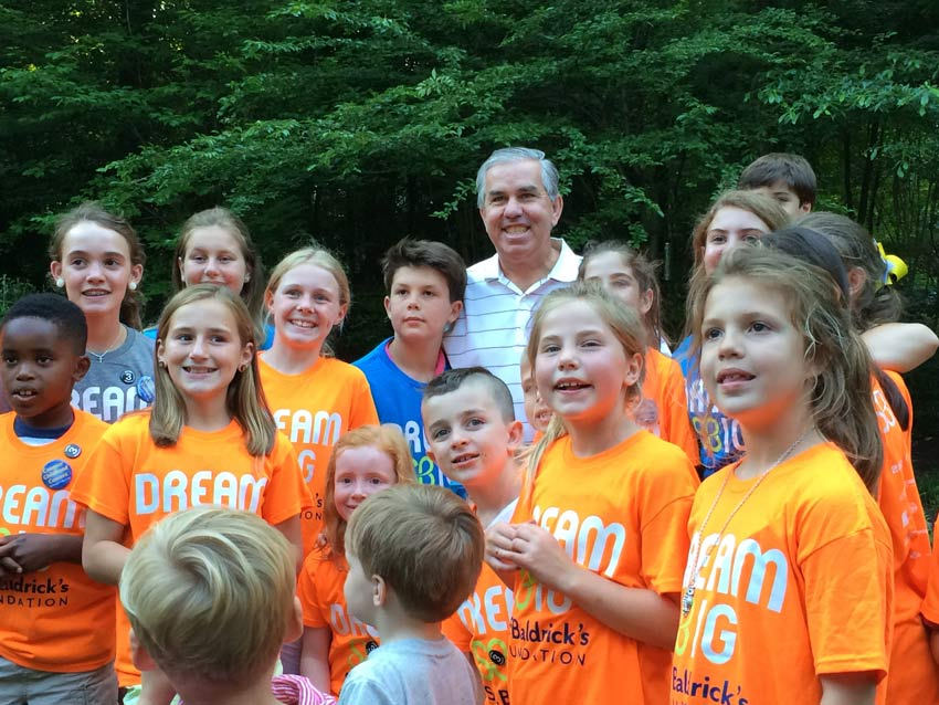 Dave Lugar stands with a whole group of children