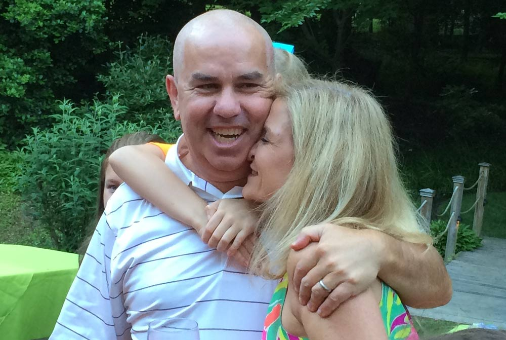 Dave Lugar and wife embracing each other at a party