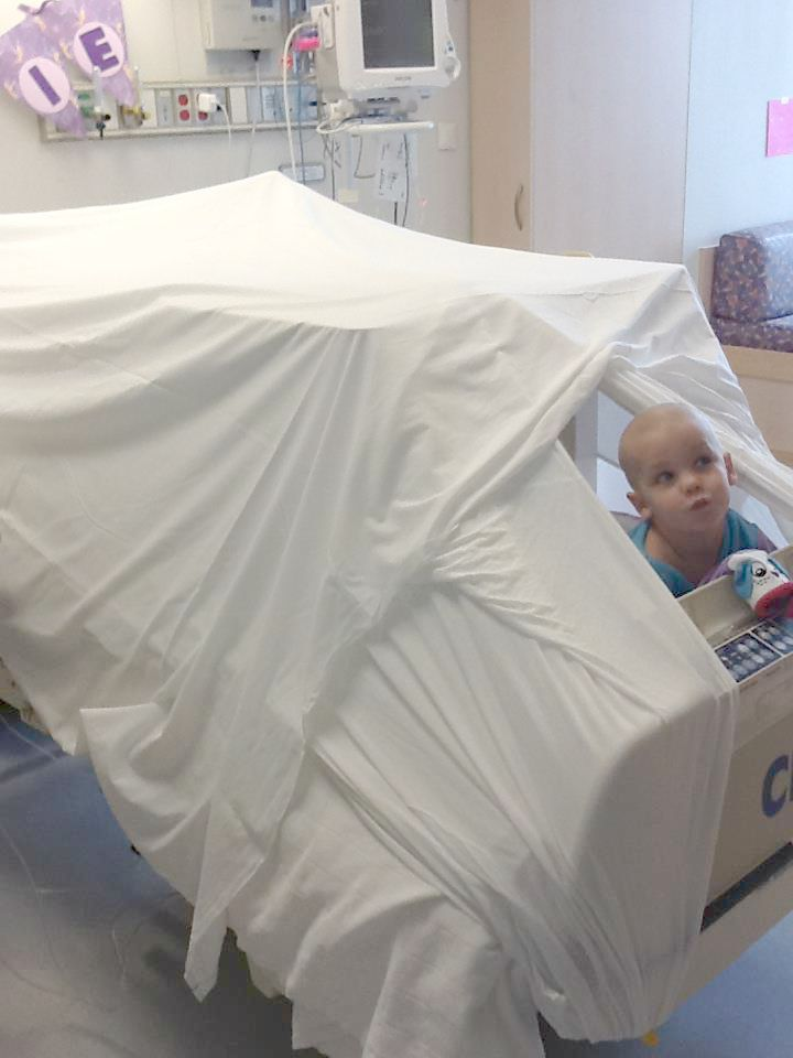 Roxie peers out of a fort made on her hospital bed