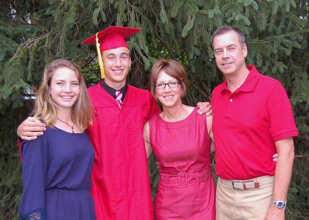 Aaron sports a cap and gown and stands with his parents and sister