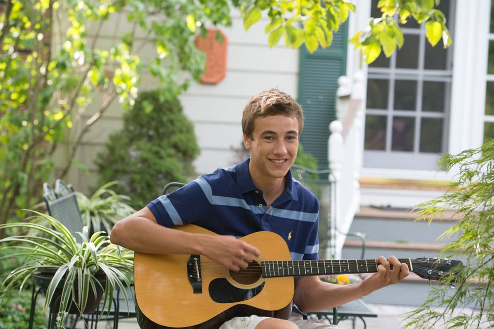 Aaron plays his guitar while smiling in the summer sun