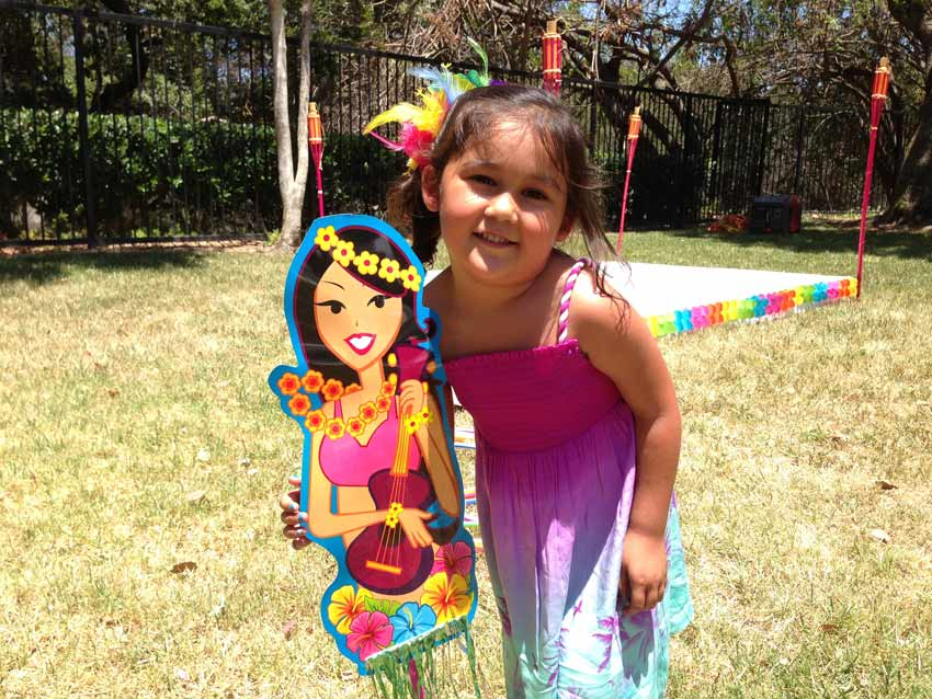 Aubrey stands next to a cutout of a hula girl holding a ukulele