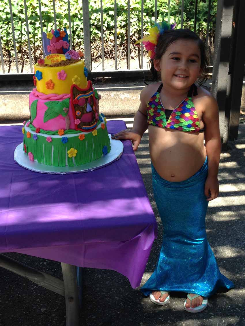 Aubrey dressed as a mermaid standing next to her cake