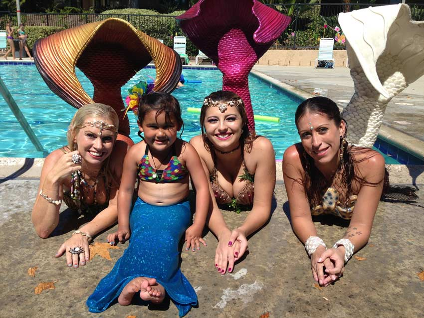 Aubrey dressed as a mermaid sitting with other mermaids by the pool