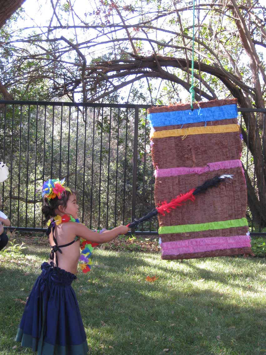 Aubrey holds a bat and swings at a piñata