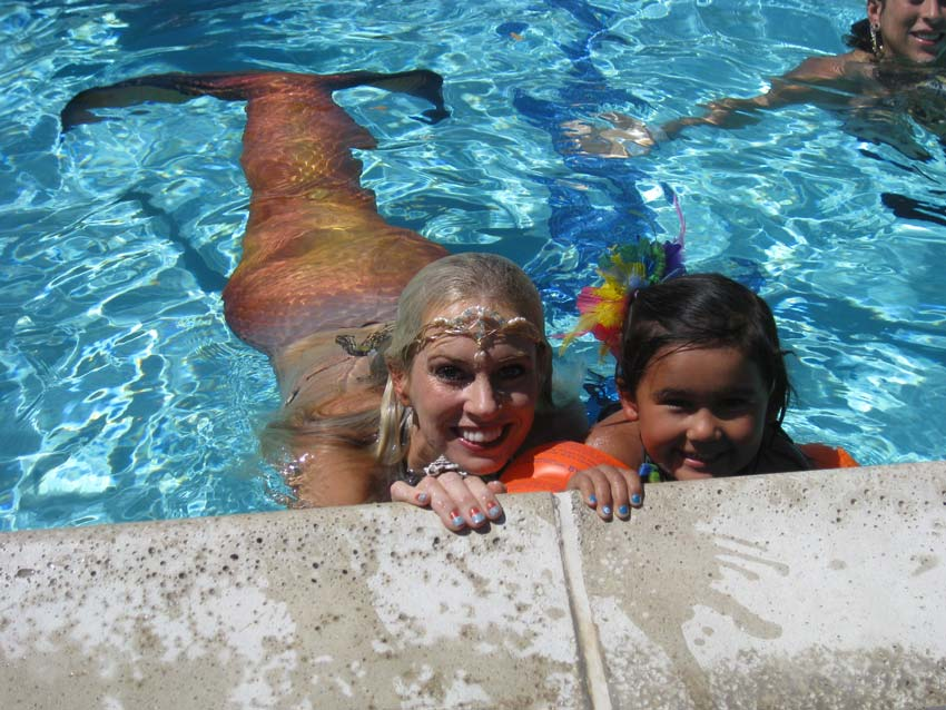 Aubrey swimming at the edge of the pool with one of her mermaid friends