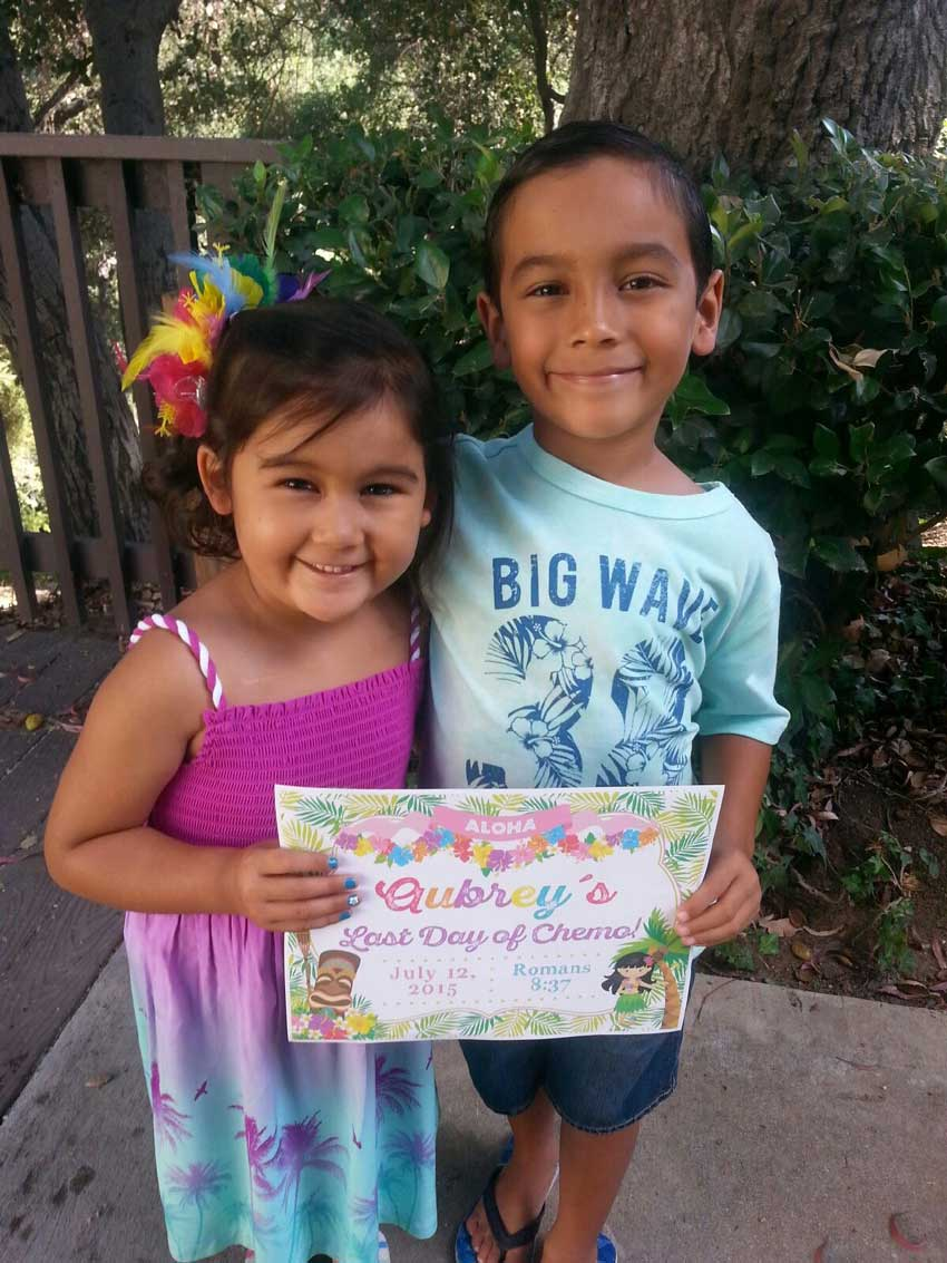 Aubrey and her brother joyfully holding a sign signifying her last day of chemo