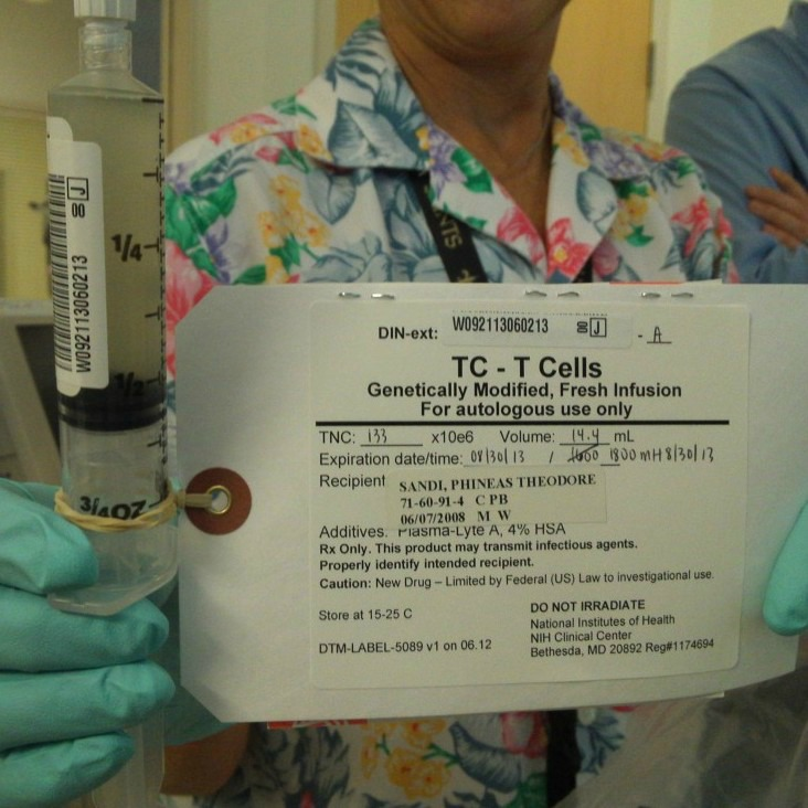 A nurse holds the single syringe of modified T cells used during Phineas's immunotherapy