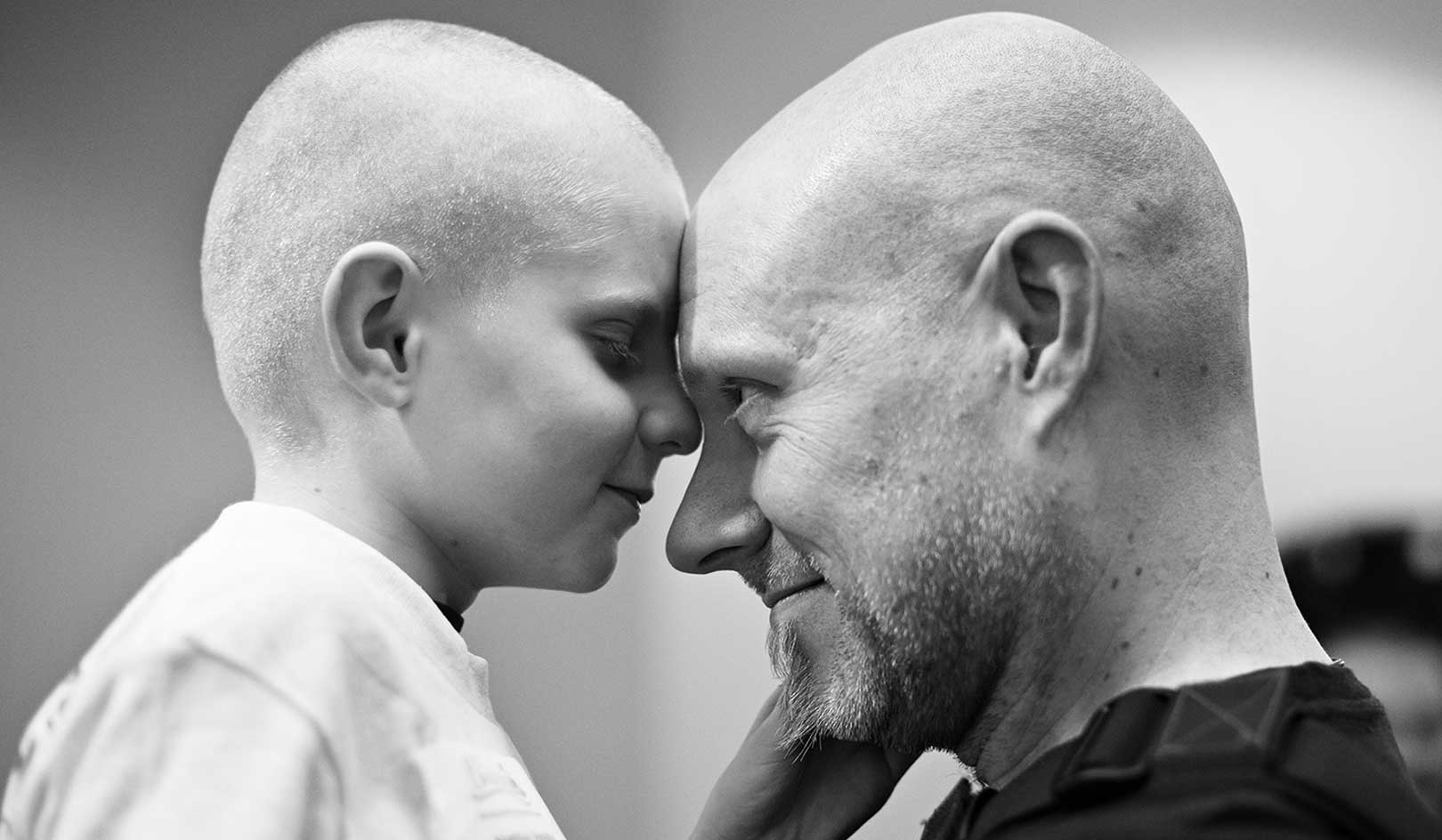 Matthias, who had retinoblastoma, hugs his father after they shaved for St. Baldrick's.