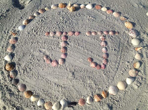 JJ's name written in shells on the beach