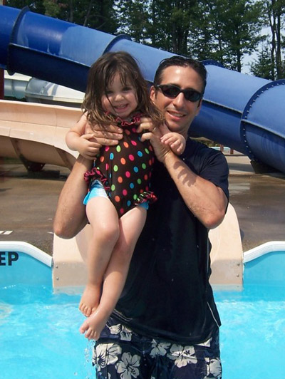 Mike holds a laughing Juliana in a pool before she was diagnosed with childhood cancer