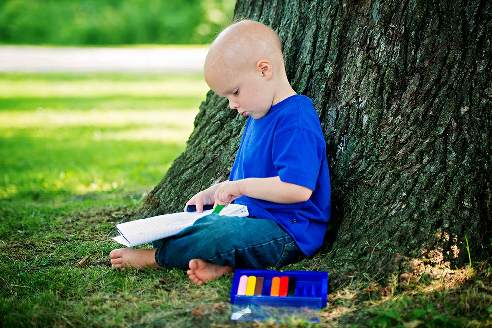 Chase sits under a tree and colors in a notebook