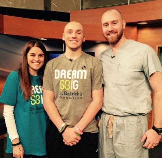 Josh stands with his barber and a fellow shavee after going bald on live TV