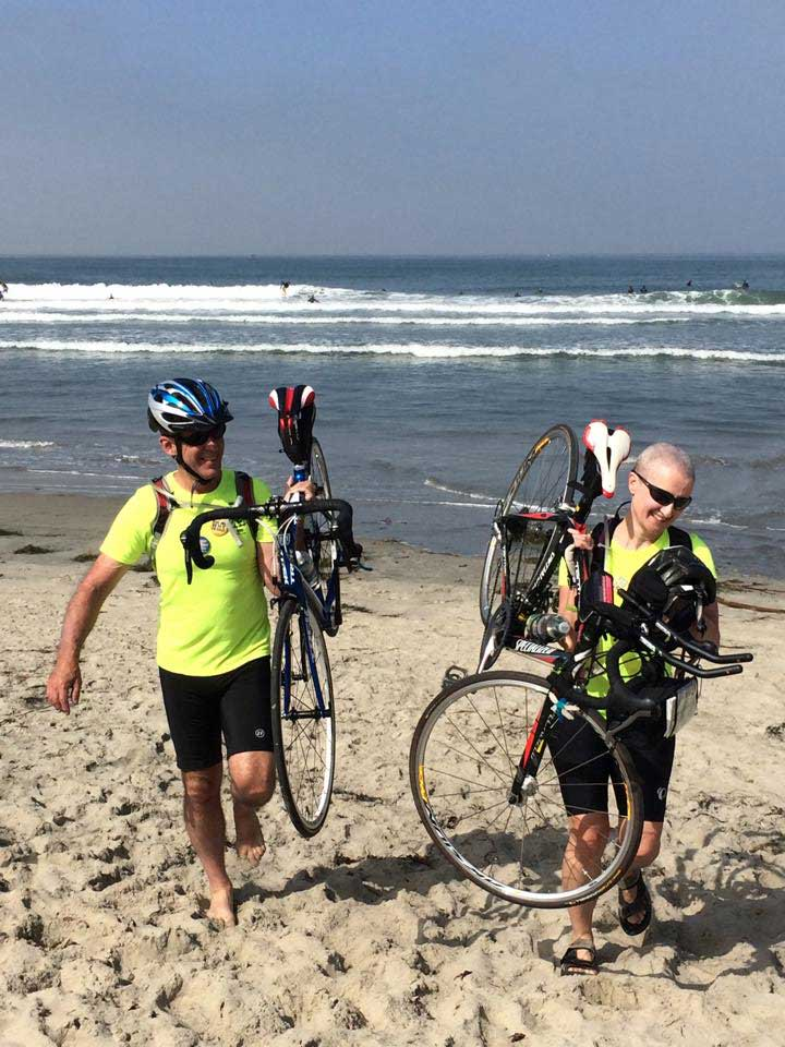 Kim and Jon lift their bikes on their shoulders at the Pacific Ocean at the start of their ride