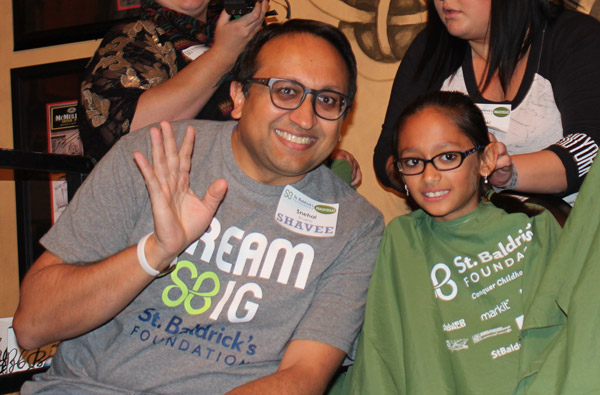 Hridi and Snehal Bhakta wave at the camera right before shaving their heads