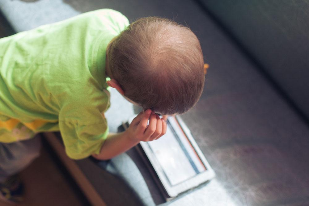 Micah plays on an iPad