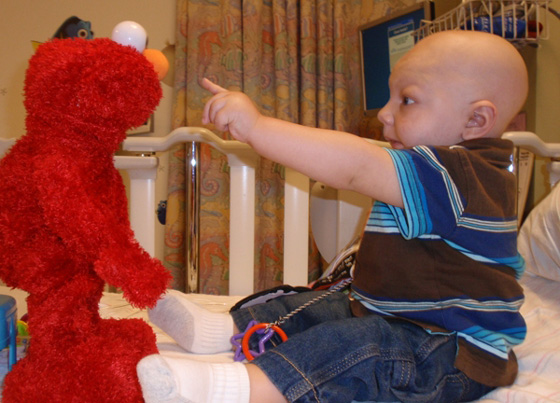 Ben giggles at Elmo during a hospital stay.