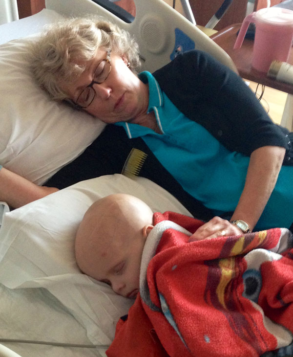 Chase and his grandma sleeping in the hospital bed while Chase was in treatment for ATRT
