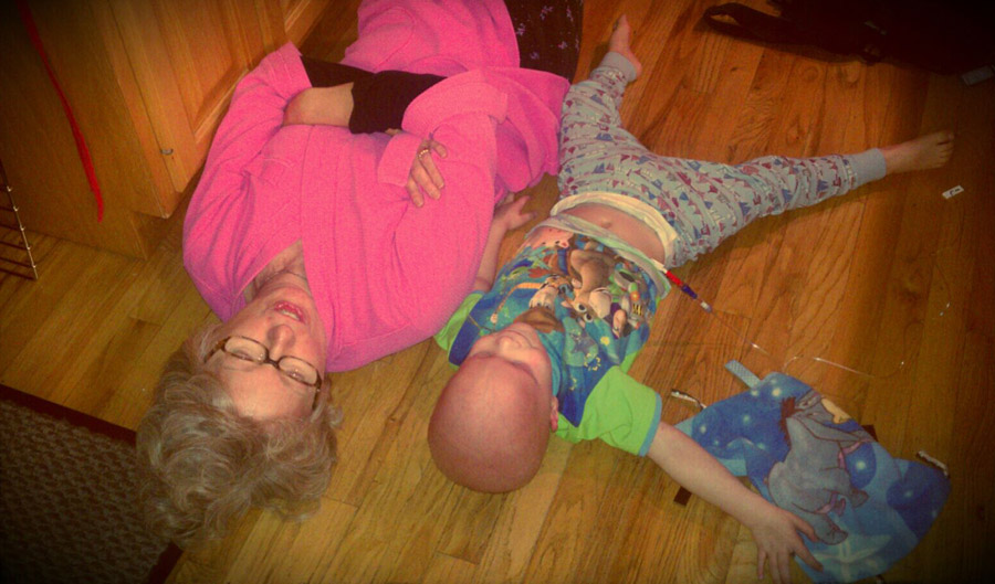 Chase and his grandma lying on the kitchen floor in their pajamas
