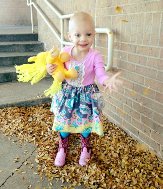 Avery smiles as she throws fall leaves in the air