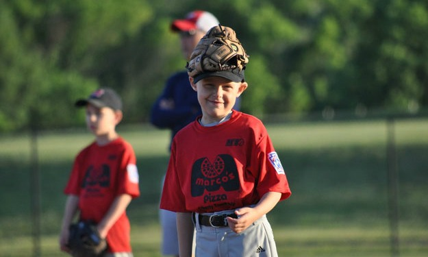 Holden smiles with a baseball glove on his head