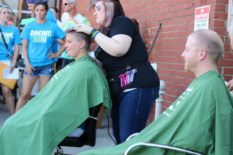 Caleb watches Ashlee brave the shave from his barber's chair