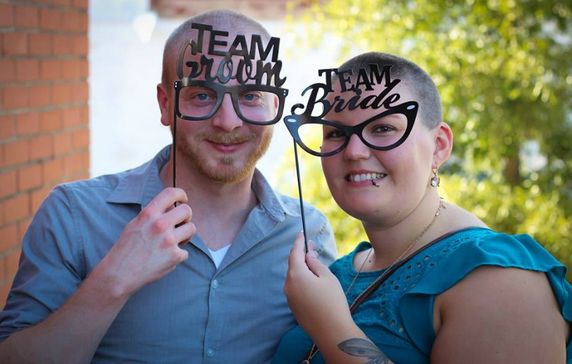 Caleb and Ashlee sport glasses that say 'Team Groom' and 'Team Bride'