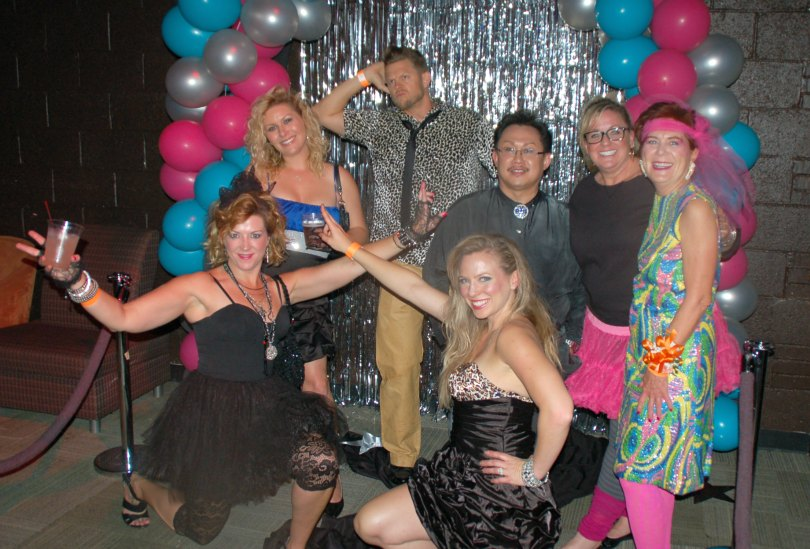 A group hams it up in front of the camera at the retro prom