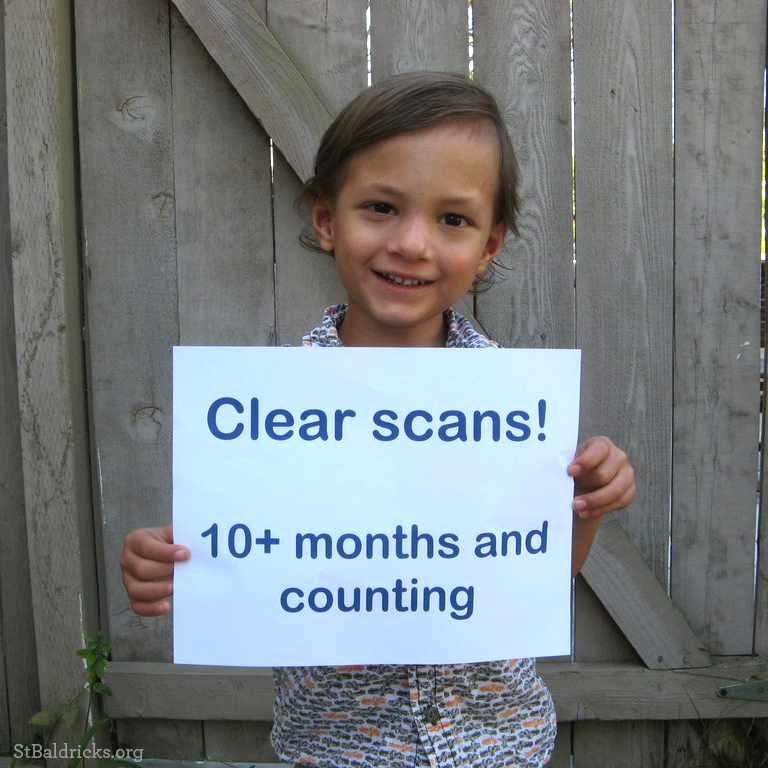 Micah holds a sign that reads, Clear Scans 10+ months and counting