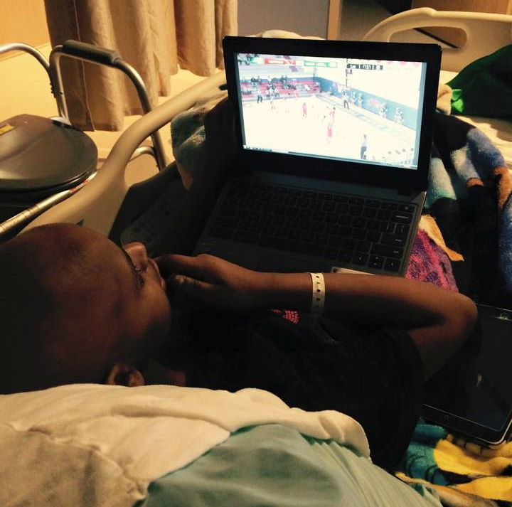 Tori watches a basketball game on a laptop in bed