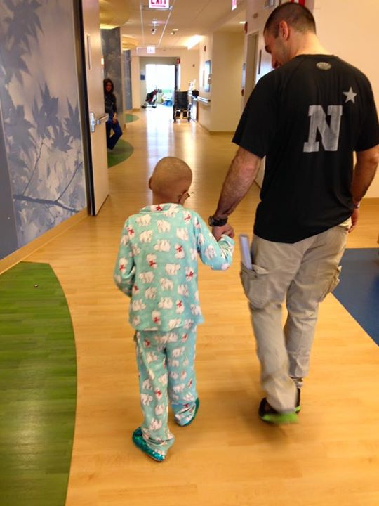 Abby and her dad walk down the hospital hallway holding hands