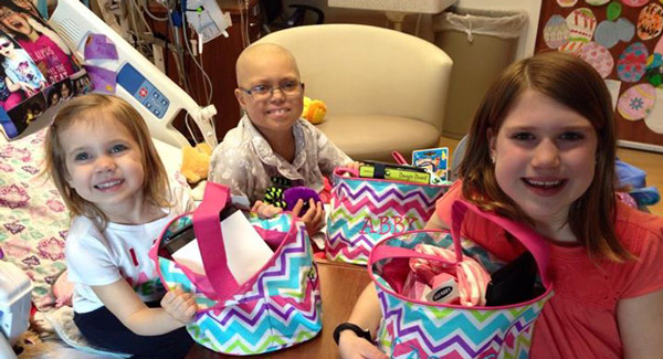 Abby and her sisters in her hospital room