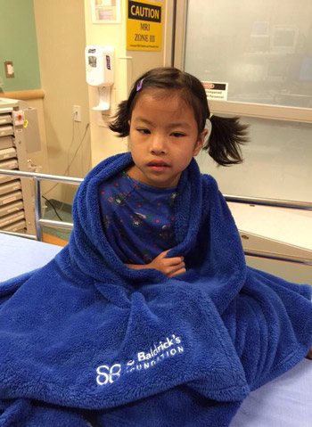 Daisy wrapped in a blue St. Baldrick's blanket before her MRI