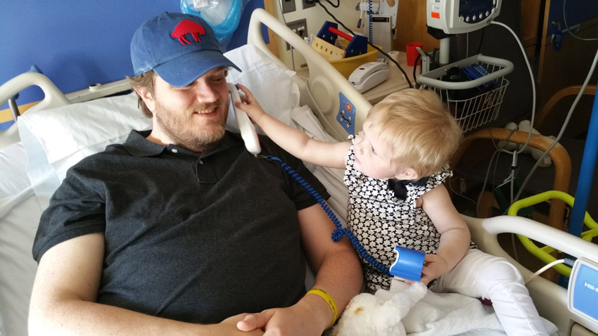 Father and child play in a hospital bed