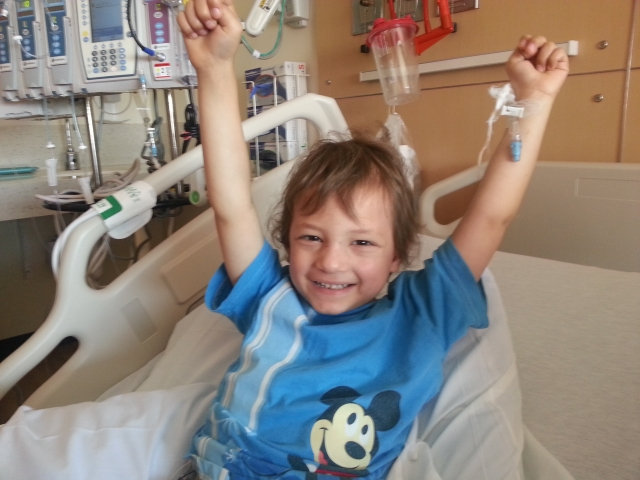 Micah triumphantly throwing his hands in the air as he prepares to leave the hospital